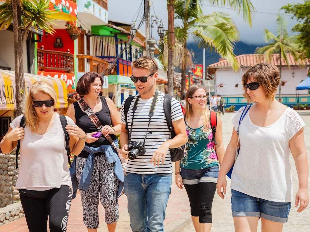 small group walking through colourful streets of guatape, antioquia