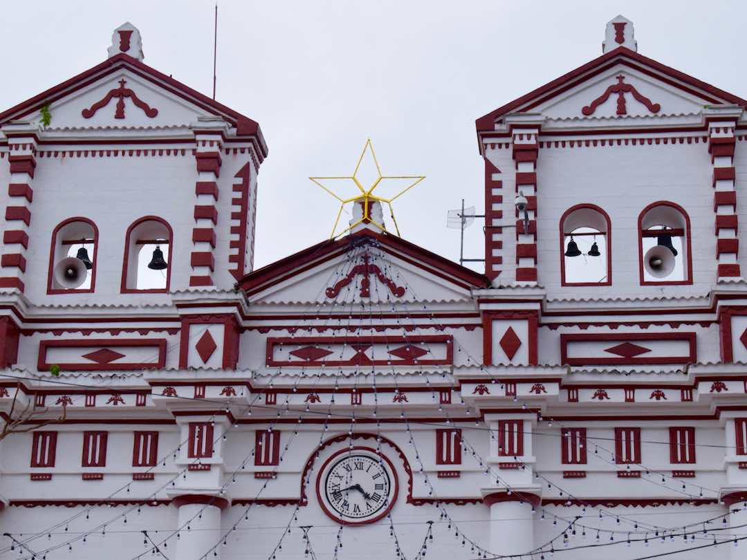 Admiring colourful church in guatape during colombia group tour