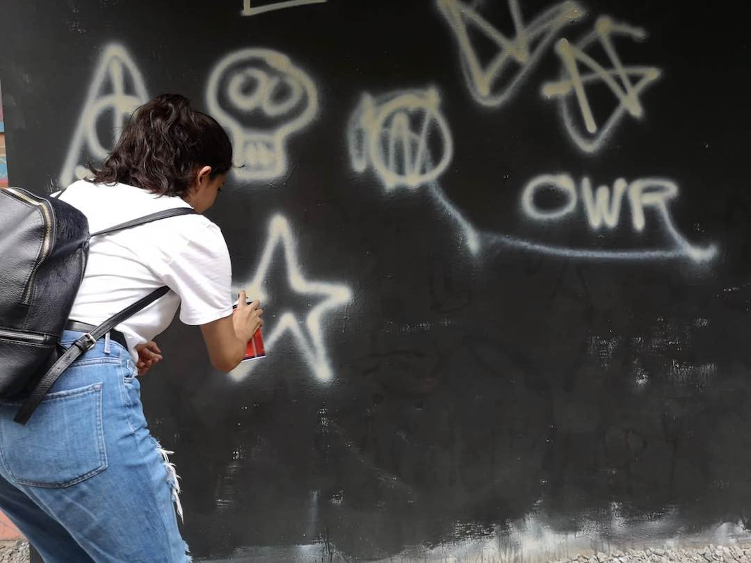 Trying graffiti during Colombia small group tour