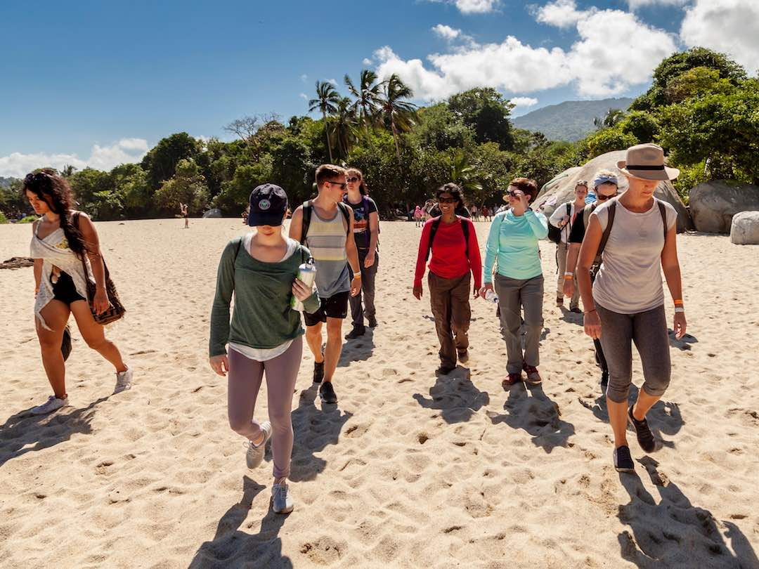 small group tour travellers hiking the beach in Parque Tayrona, Colombia